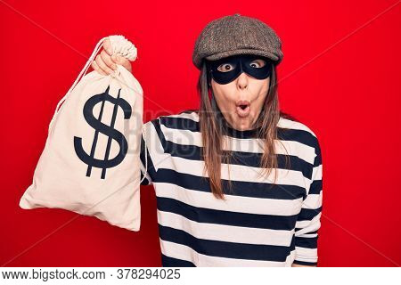 Young beautiful burglar woman wearing cap and mask holding money bag with dollar symbol scared and amazed with open mouth for surprise, disbelief face
