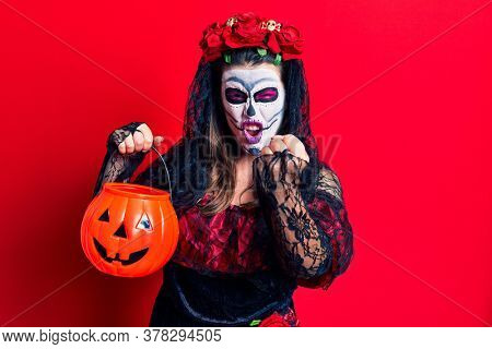 Young woman wearing day of the dead costume holding pumpkin annoyed and frustrated shouting with anger, yelling crazy with anger and hand raised