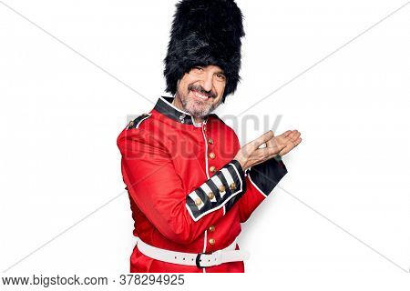 Middle age handsome wales guard man wearing traditional uniform over white background pointing aside with hands open palms showing copy space, presenting advertisement smiling excited happy