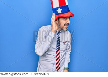 Middle age handsome patriotic man wearing united states hat and tie over blue background smiling with hand over ear listening and hearing to rumor or gossip. Deafness concept.