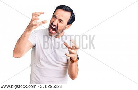 Middle age handsome man wearing casual t-shirt shouting frustrated with rage, hands trying to strangle, yelling mad