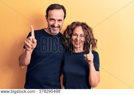 Middle age beautiful couple wearing t-shirt standing over isolated yellow background smiling with an idea or question pointing finger up with happy face, number one