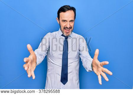 Middle age handsome business man wearing elegant tie standing over isolated blue background looking at the camera smiling with open arms for hug. Cheerful expression embracing happiness.