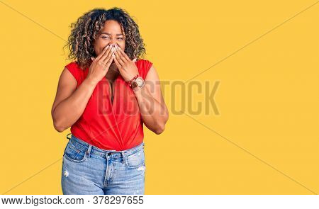 Young african american plus size woman wearing casual style with sleeveless shirt laughing and embarrassed giggle covering mouth with hands, gossip and scandal concept