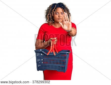 Young african american plus size woman holding supermarket shopping basket with open hand doing stop sign with serious and confident expression, defense gesture