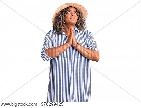 Young african american plus size woman wearing summer hat begging and praying with hands together with hope expression on face very emotional and worried. begging.
