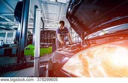 Worker Checks And Adjusts The Headlights Of A Cars Lighting System