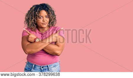 Young african american plus size woman wearing casual clothes pointing to both sides with fingers, different direction disagree