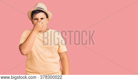Little boy kid wearing summer hat and hawaiian swimsuit smelling something stinky and disgusting, intolerable smell, holding breath with fingers on nose. bad smell