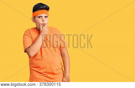 Little boy kid wearing sportswear looking fascinated with disbelief, surprise and amazed expression with hands on chin