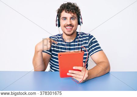 Young caucasian man with curly hair using touchpad sitting on the table pointing finger to one self smiling happy and proud