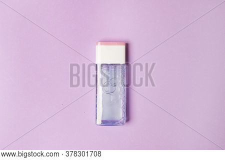 Bottle With Tonic For Health Care On Purple Colored Paper Background.