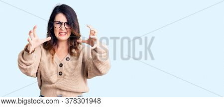 Beautiful young brunette woman wearing casual clothes and glasses shouting frustrated with rage, hands trying to strangle, yelling mad