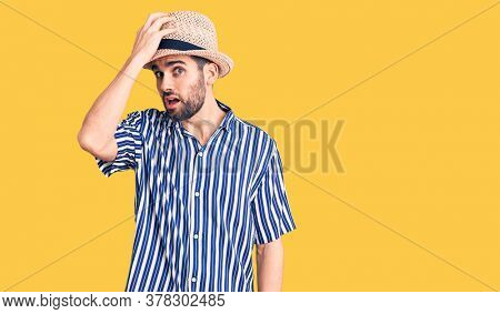 Young handsome man with beard wearing summer hat and striped shirt surprised with hand on head for mistake, remember error. forgot, bad memory concept.