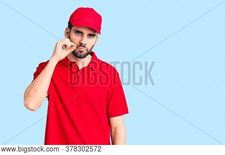 Young handsome man with beard wearing delivery uniform mouth and lips shut as zip with fingers. secret and silent, taboo talking