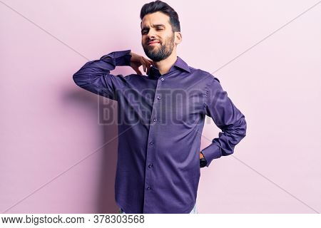 Young handsome man with beard wearing casual shirt suffering of neck ache injury, touching neck with hand, muscular pain