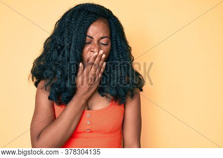 Beautiful african woman wearing casual clothes bored yawning tired covering mouth with hand. restless and sleepiness.