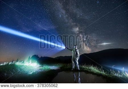 Astronaut Illuminating Fantastic Night Sky With Flashlight. Cosmonaut Wearing White Space Suit And H