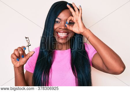 Young african american woman holding eyelash curler smiling happy doing ok sign with hand on eye looking through fingers