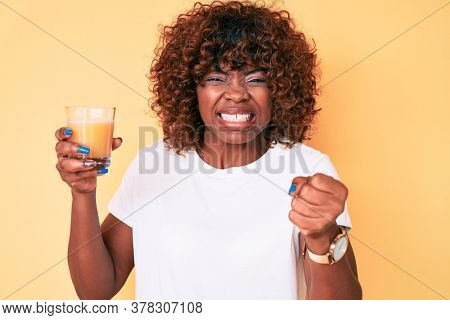 Young african american woman drinking glass of orange juice annoyed and frustrated shouting with anger, yelling crazy with anger and hand raised