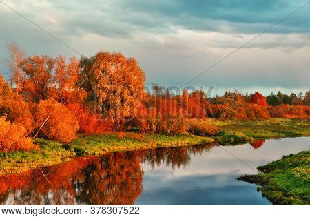 Autumn colored water view of sunset autumn picturesque nature with autumn river and yellowed autumn trees in the sunset. Soft filter applied. Autumn colorful nature, autumn landscape