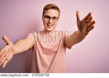 Young handsome redhead man wearing casual t-shirt standing over isolated pink background looking at the camera smiling with open arms for hug. Cheerful expression embracing happiness.