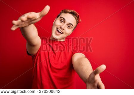 Young handsome redhead man wearing casual t-shirt over isolated red background looking at the camera smiling with open arms for hug. Cheerful expression embracing happiness.