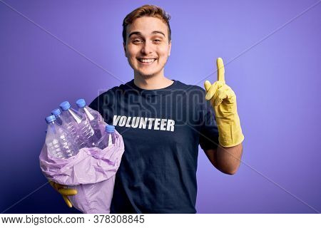 Young handsome redhead volunteer man doing volunteering holding bag with plastic bottles surprised with an idea or question pointing finger with happy face, number one