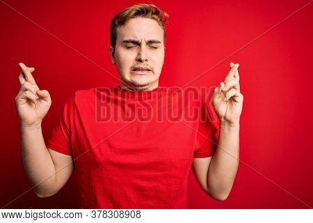 Young handsome redhead man wearing casual t-shirt over isolated red background gesturing finger crossed smiling with hope and eyes closed. Luck and superstitious concept.