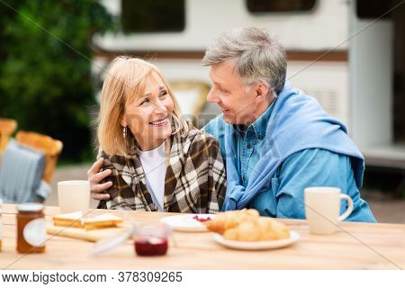 Mature Love. Loving Husband And His Beautiful Wife Having Breakfast Together On Camping Trip Near Th