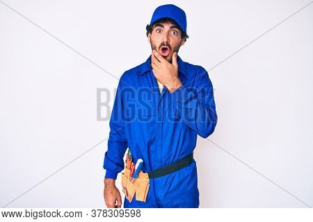 Handsome young man with curly hair and bear weaing handyman uniform looking fascinated with disbelief, surprise and amazed expression with hands on chin