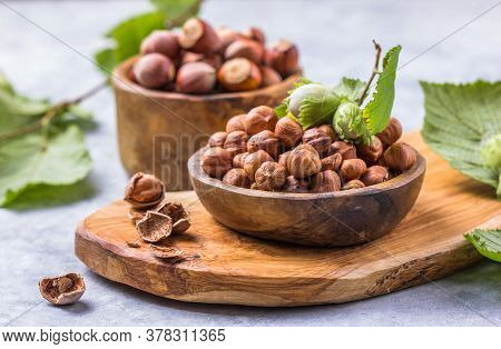 Hazelnuts With Peeled Hazelnut And Leaf  In Brown Bowl On Concrete Background. Hazelnuts With Peeled