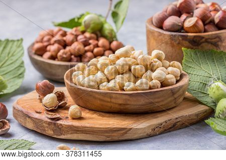 Hazelnuts With Peeled Hazelnut And Leaf  In Brown Bowl On Concrete Background. Top View Of Hazelnuts