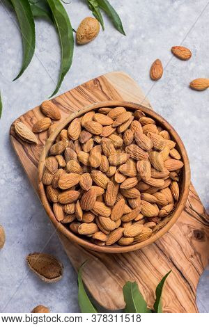 Peeled Whole Almonds  In Bowl With Leaf. Peeled Whole Almonds And Unshelled Almonds In Bowl With Lea
