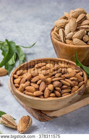 Peeled Whole Almonds And Unshelled Almonds In Bowl With Leaf.  Pile Of The Dried Peeled Almonds And