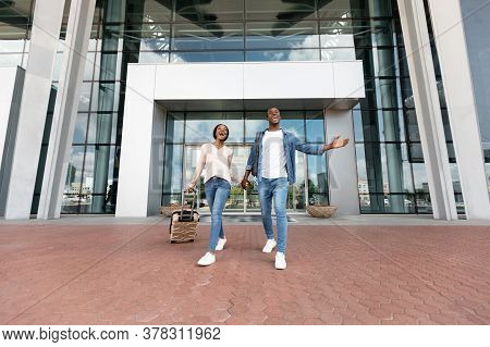 After Arrival. Joyful Black Couple Leaving Airport Terminal With Suitcases, Low Angle View, Free Spa