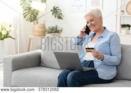 Happy Senior Woman With Laptop And Credit Card Talking On Cellphone At Home, Transferring Money Onli