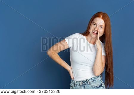 Whispering A Secret. Caucasian Young Girls Portrait On Blue Background. Beautiful Female Redhair Mod