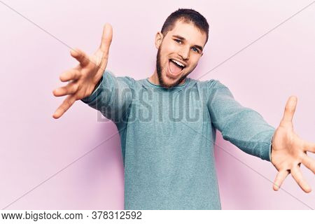 Young handsome man wearing casual sweater looking at the camera smiling with open arms for hug. cheerful expression embracing happiness.