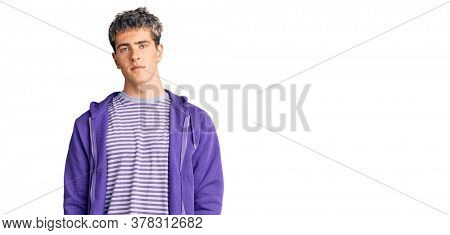 Young handsome man wearing casual purple sweatshirt relaxed with serious expression on face. simple and natural looking at the camera.