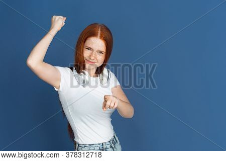 Choosing You. Caucasian Young Girls Portrait On Blue Background. Beautiful Female Redhair Model With