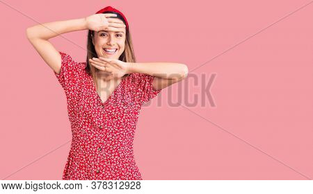 Young beautiful women wearing dress and diadem smiling cheerful playing peek a boo with hands showing face. surprised and exited