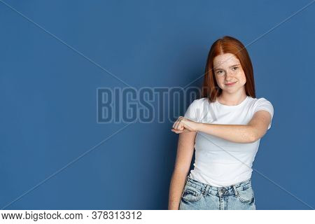 Fist Bump. Caucasian Young Girls Portrait On Blue Background. Beautiful Female Redhair Model With Cu