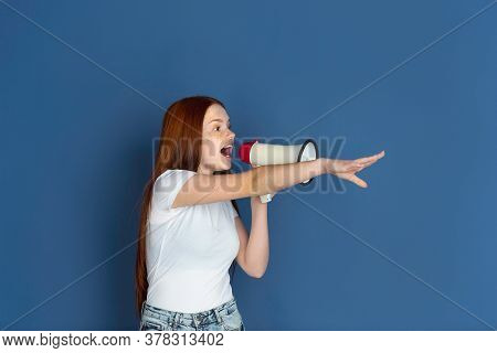 Shouting With Mouthpeace. Caucasian Young Girls Portrait On Blue Background. Beautiful Female Redhai