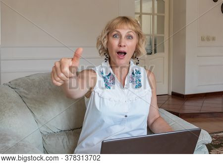 A Pretty Woman Of Fifty Is Sitting In An Armchair With A Laptop And Is Delighted With Something
