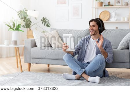 Positive Guy Having Videocall, Using Digital Tablet And Wireless Headset At Home, Copy Space