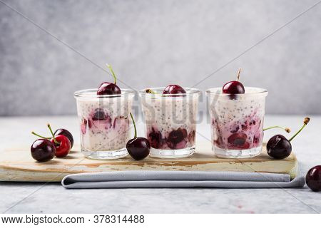 Chia Pudding With Cherry Berries, Natural Yogurt,  In A Glass On A Grey Surface. Selective Focus. He