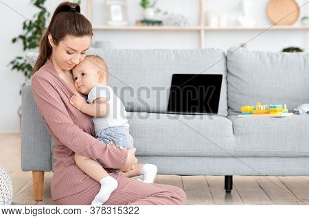 Mother-baby Emotional Attachment. Loving Young Mom Hugging Her Adorable Toddler Son At Home, Sitting