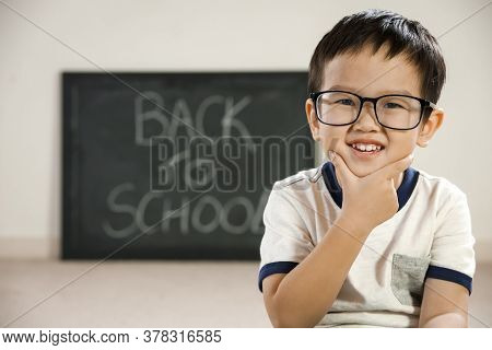 Smiling Asian Boy With School Blackboard Behind, Back To School Education Concept, Intelligent Happy
