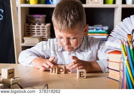 Wooden Cubes With Word Home In Hands Of Little Boy At Home. Conceptual Image About Child Rights, Edu